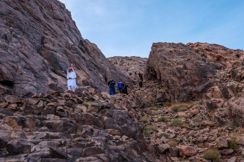 Паломники, ведомые бедуином, спускаются с горы