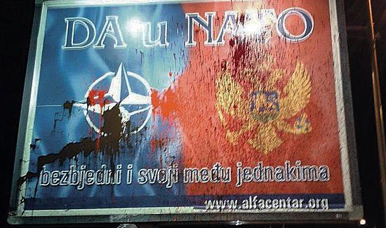"""Облитый краской стенд с рекламой НАТО в Подгорице. Надпись на плакате: """"Да - в НАТО."""""""