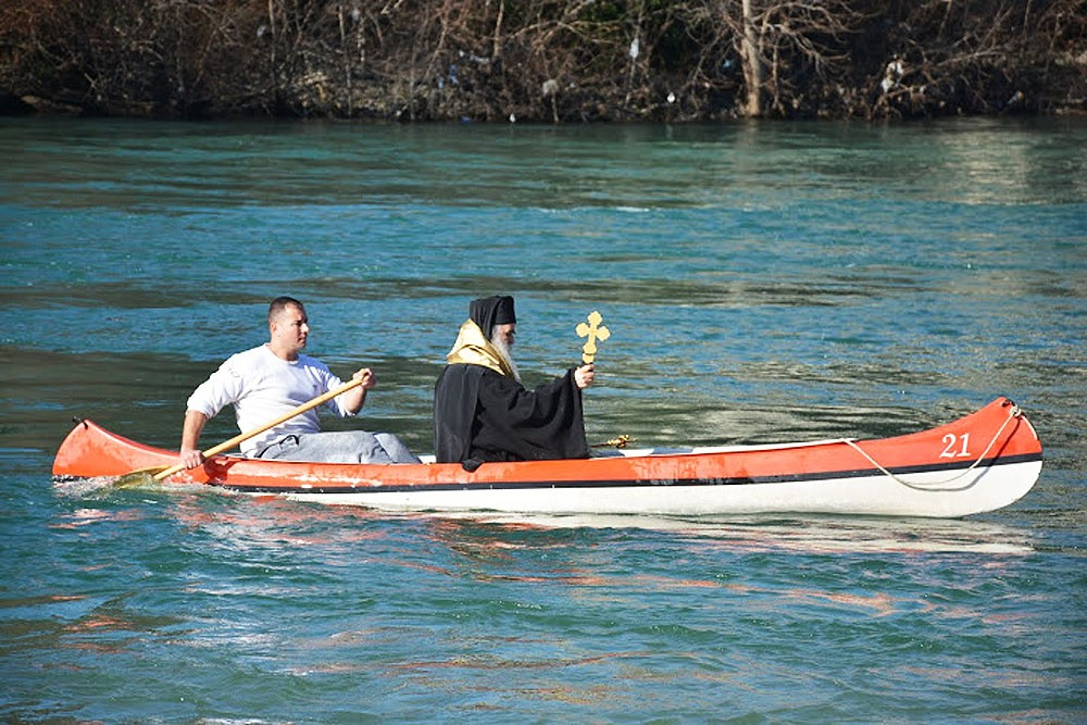 Metropolitan Amfilohije canoes out with the cross to the middle of the river.