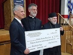 Bishop Paul presents $31K check to OCMC to buy motorbikes for Kenyan clergy