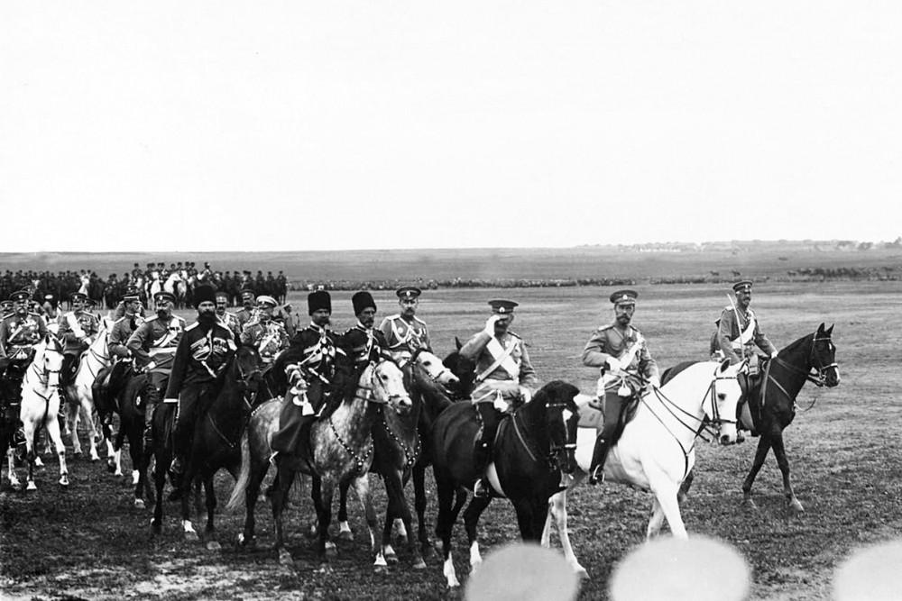 Император Николай II и датский король Фридрих VIII со свитой на военном поле объезжают фронт выстроенных на смотр войск. 7 июля 1909 г.