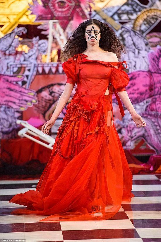 Эта модель одета в ритуальное красное платье, а на лице у нее – большая пентаграмма. Большинство моделей превратились в магические предметы, словно все это часть одного оккультного ритуала