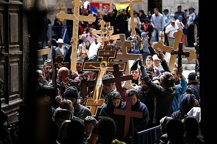 Pilgrims carrying wooden crosses enter the Holy Sepulchre Church during the Orthodox Good Friday procession. Photo: Thomas Coex/AFP