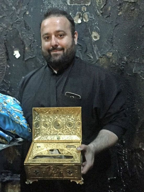 Father Michael Pfaromatis with the holy relics retrieved from the church's burnt altar. Photo: www.abc.net.au