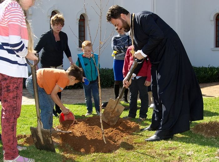 Planting trees with the parishioners near the church.
