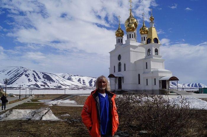 Российский православный путешественник В.А. Ефремов на фоне храма Воздвижения Креста Господня в посёлке Эгвекинот