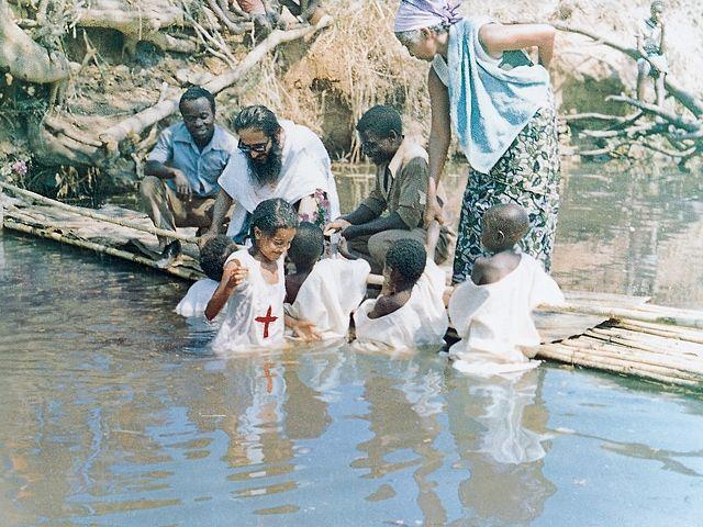 Fr. Cosmas baptizes children