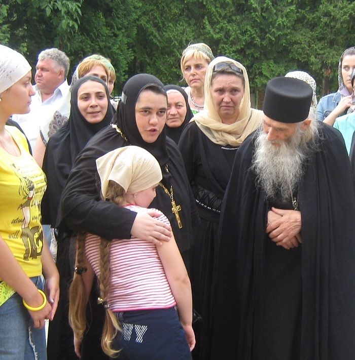 Mother Nonna leads Tamila, daughter of the killed teacher Alena Dzutseva, up to take Elder Iliy's blessing