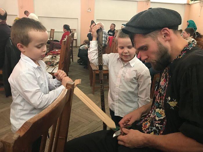 Денис Антипов в Луге на фестивале объясняет детям значение символов на тростке