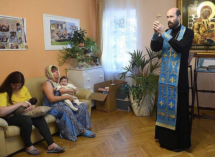 Отец Михаил и его подопечные во время утренней службы в «Доме для мамы». Фото: Кристина Кормилицына, Коммерсантъ