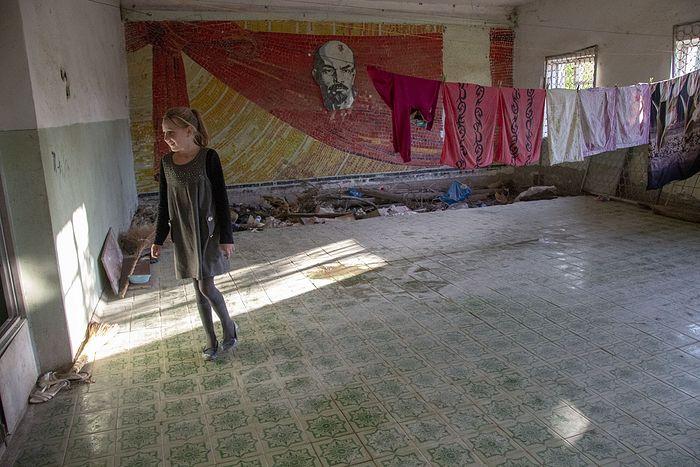 Бывший актовый зал административного здания, которое после войны переоборудовали в жилой барак. Сейчас в бараке на цементном полу живут люди, пока они заняты своими делами, Ленин приглядывает за бельем и детьми