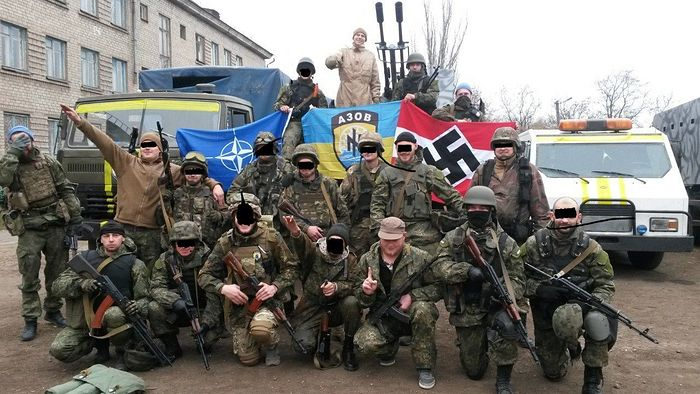Azov battalion flag in the center beside a swastika and a NATO flag. Photo: Scott.net.
