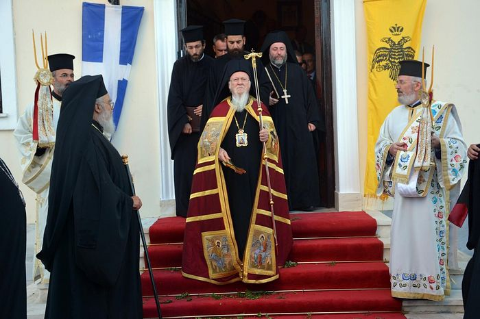 The ecumenical patriarch Bartholomew with the two-headed eagle and Greek flags. Photo: www.amna.gr