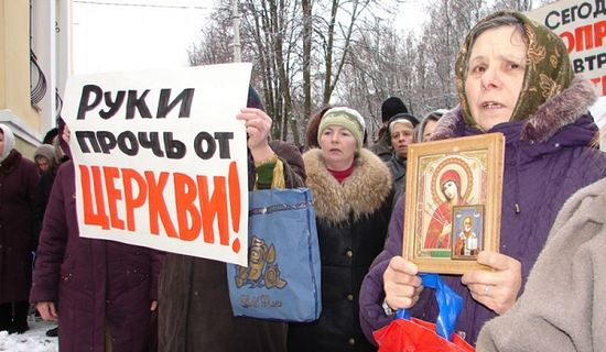 "Women defend their church with icons and a sign that reads ""Hands off the church."" Photo: politnavigator.net"
