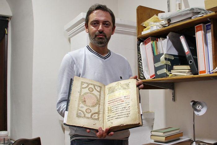 Сергей Шумило держит в руках Афонский помянник