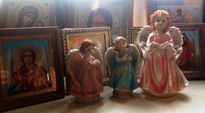 Фигурки «ангелов» в церковной лавке рядом с православными иконами