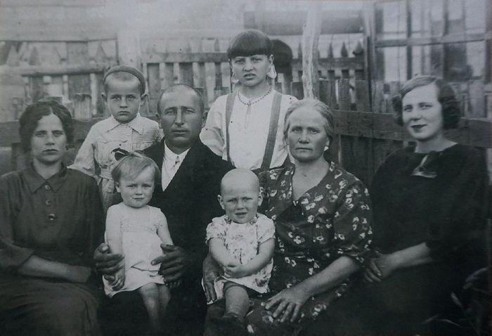 Семья Баклановых. Нина в нижнем ряду вторая слева на коленях у папы Якова перед отъездом его на фронт в 1943 г.