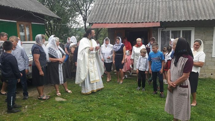 Archpriest Ilia Urusky, rector of the persecuted UOC-MP St. Michael's Orthodox community, with his flock after a service in one of the houses of the village of Shandrovets