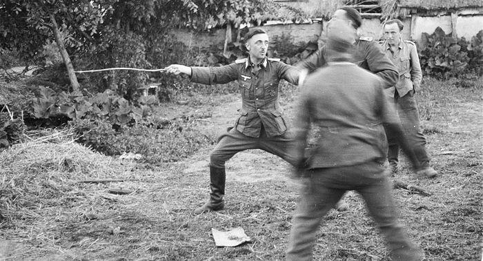 Выпивающие офицеры и унтер-офицеры вермахта на сельском дворе в оккупированной деревне в Курской области (ныне район Белгородской области). 1943. waralbum.ru
