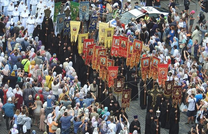 Members of the canonical church carrying religious banners and crosses.