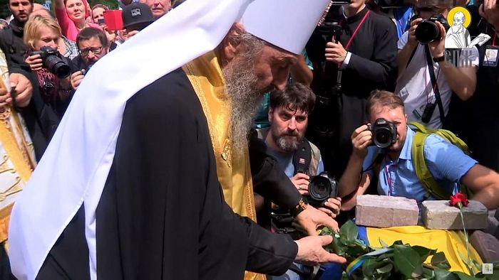 Metropolitan Onuphry laying flowers wrapped in a Ukrainian flag ribbon at a Ukrainian memorial in 2018.