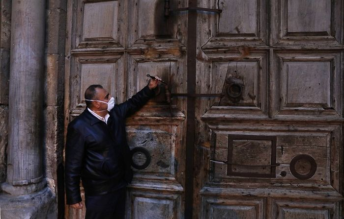 Adeeb Joude, the custodian in charge of the ancient key to the Church of the Holy Sepulchre, closes the entrance gate to the church due to the coronavirus (COVID-19) pandemic, in Jerusalem's Old City on March 25, 2020. (Ahmad GHARABLI / AFP)