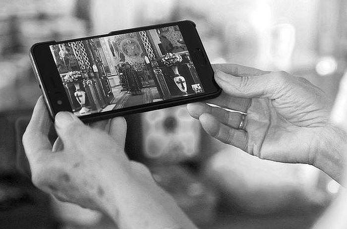 Женщина смотрит онлайн-трансляцию службы из храма. Фото Виталий Тимкив/РИА Новости