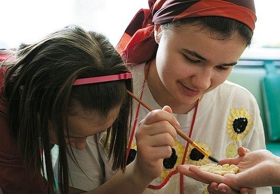 Η Άνετσκα, η μικρότερη κόρη, και η Λιούμπα Σοκολόβ αλείφουν με αυγό τα στολίδια για τα τσουρέκια