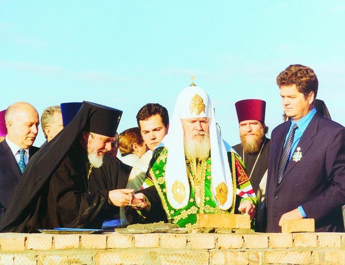 Святейший Патриарх Алексий II закладывает капсулу с посланием потомкам в основание храма Георгия Победоносца. Слева – владыка Сергий, справа – Вячеслав Сонин. 19 октября 1999 года