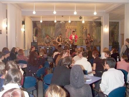 Интернет-кафе РГГУ. Рок-группа с гитарами выступает на фоне копии сюжета «Причащение апостолов»