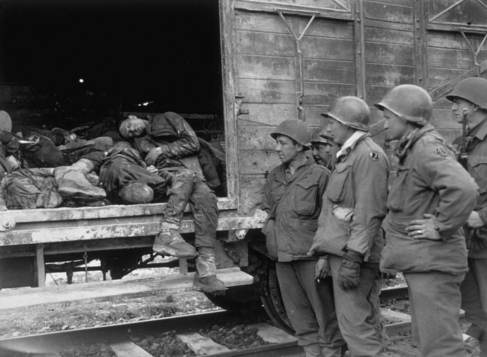 Soldiers of the U.S. 42nd infantry division at a train car with the bodies of prisoners from Dachau