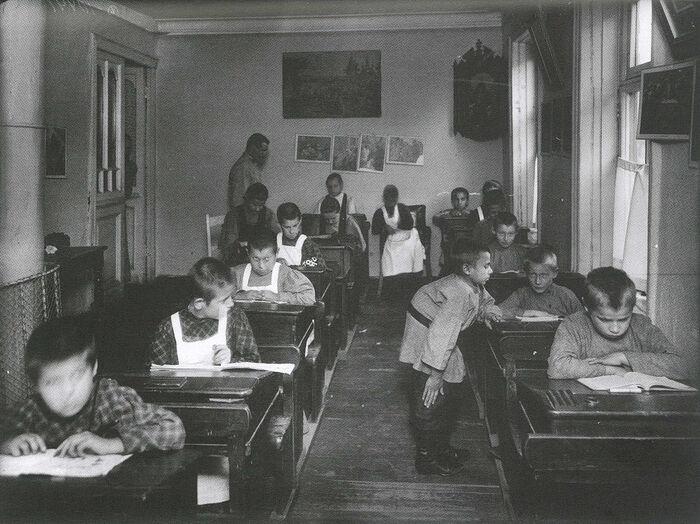 Ученики в классе со служителем-мужчиной. На стенах иллюстрации к Библии. Фото: Ателье К. Буллы, 1907 г