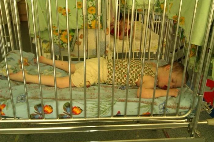 Глебу 7 лет. Он в детской кровати с высокими бортиками в детском доме