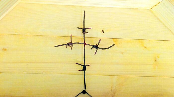 Крест из колючей проволоки ограждения территории в беседке-часовне