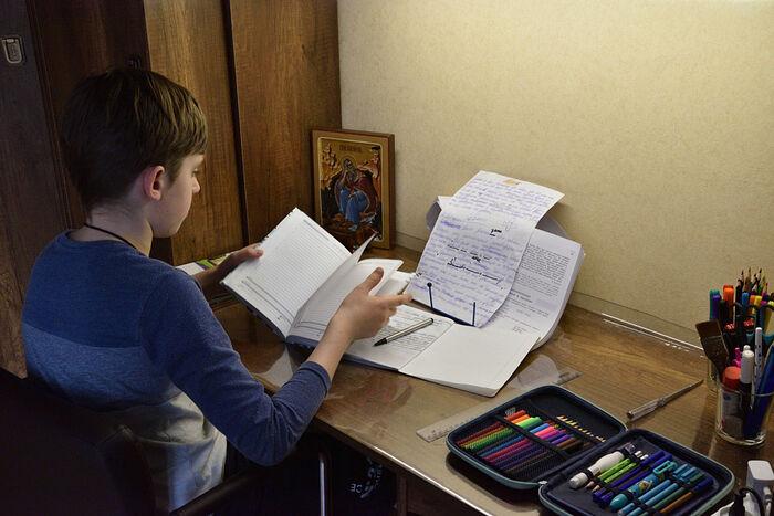 Старший Илья в своей комнате за уроками
