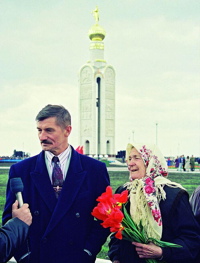 В.М. Клыков с матерью на фоне белокаменной звонницы на Прохоровском поле