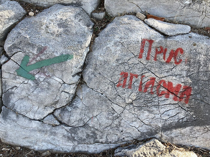 A sign painted on the rocks: 'Pros agiasma' ('To the sacred spring')